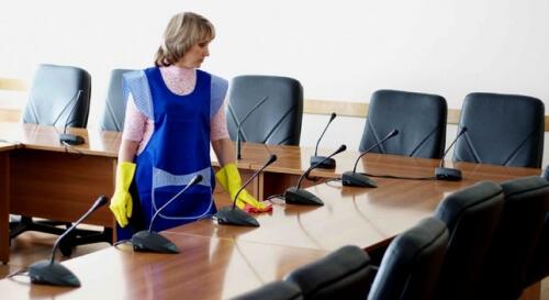 Девушка протирает стол в переговорной