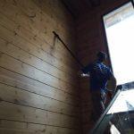 Мойщик чистит стены внутри дома
