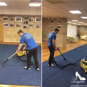 Человек чистит большое ковровое покрытие в холле