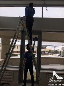 Два человека моют стекла
