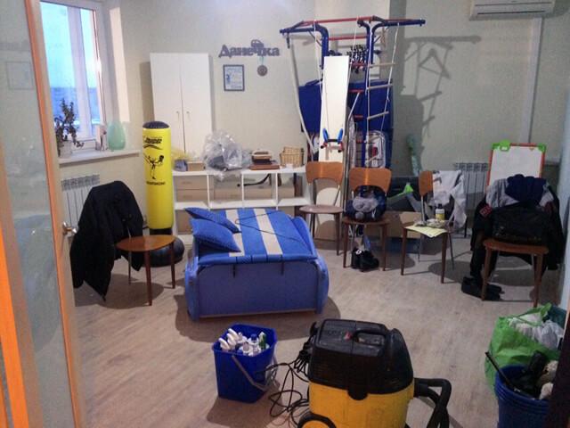 Захламленная комната со спорткомплексом и белым шкафом
