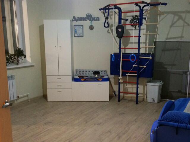 Комната со спорткомплексом и белым шкафом