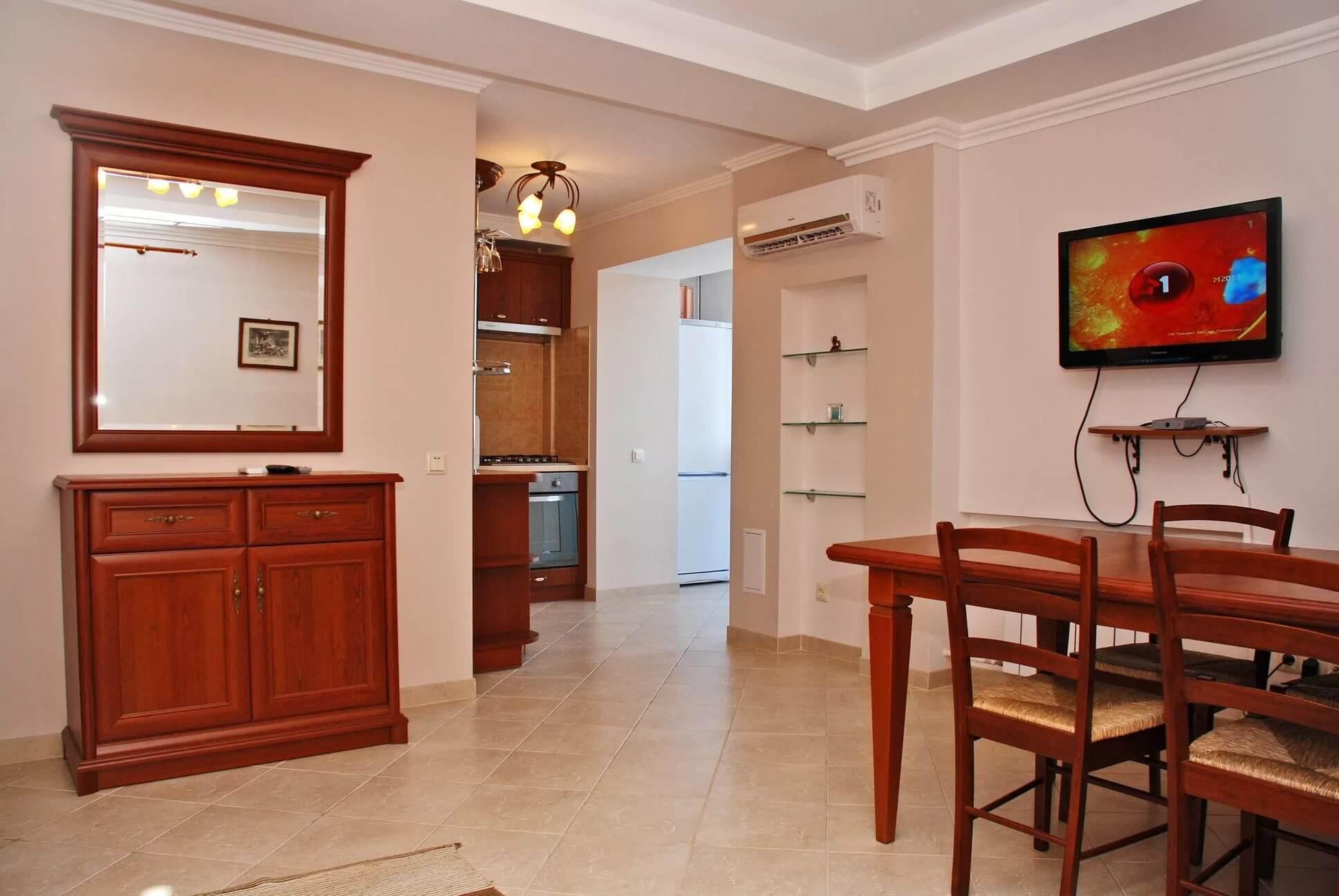 Стол, стулья, телевизор, шкафчик с зеркалом в квартире