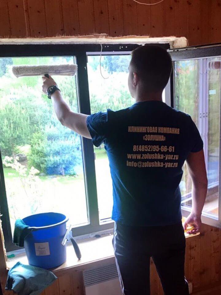 Мужчина моет оконное стекло