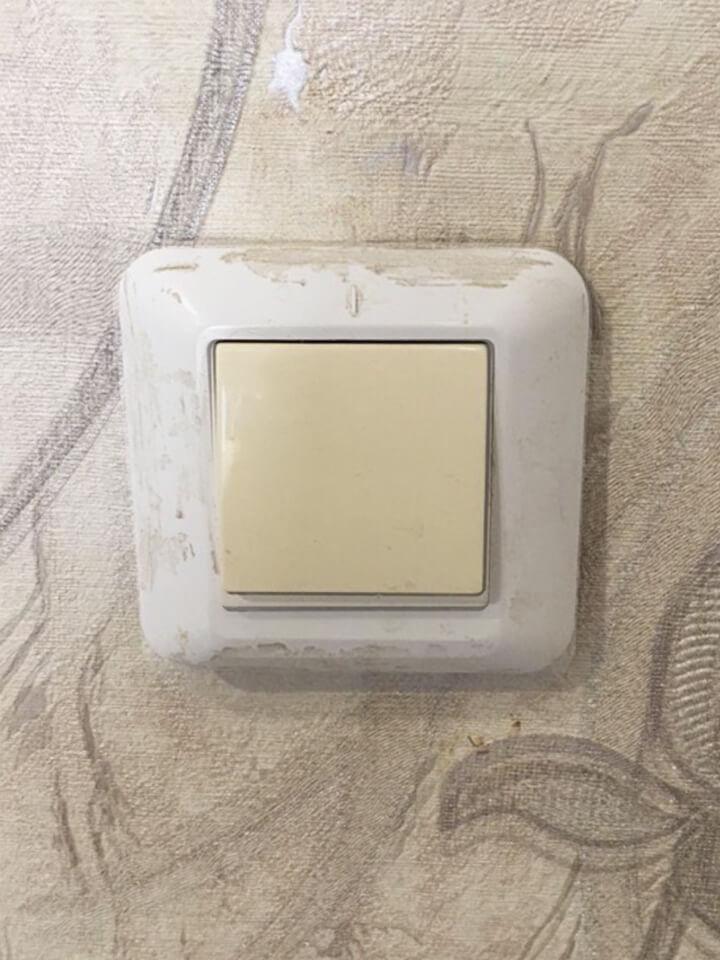 Электрический выключатель с пятнами краски и грязи