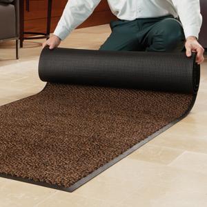 Человек раскатывает коричневый коврик