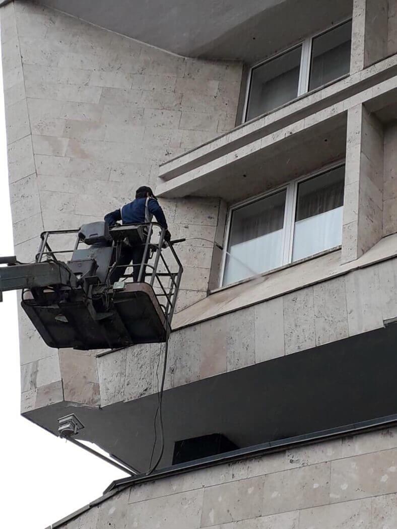 Мойщик чистит фасад дома с подъемника