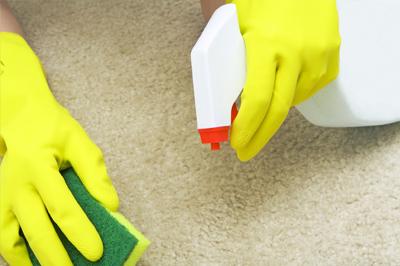 Руки в желтых перчатках с губкой и чистящим средством