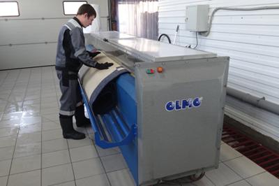 Сотрудник загружает ковер в аппарат для чистки
