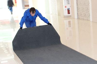 Человек расстилает ковровое покрытие
