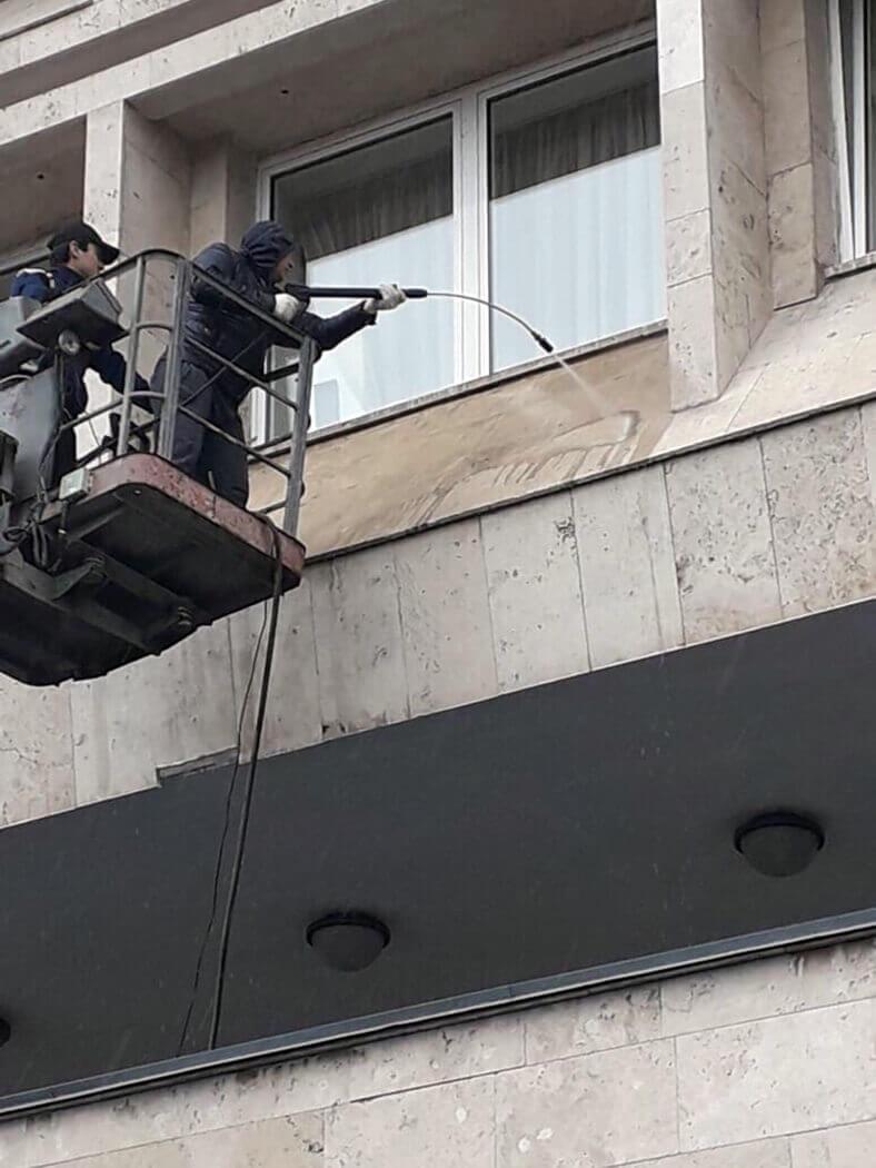 Два мойщика чистят фасад дома с подъемника