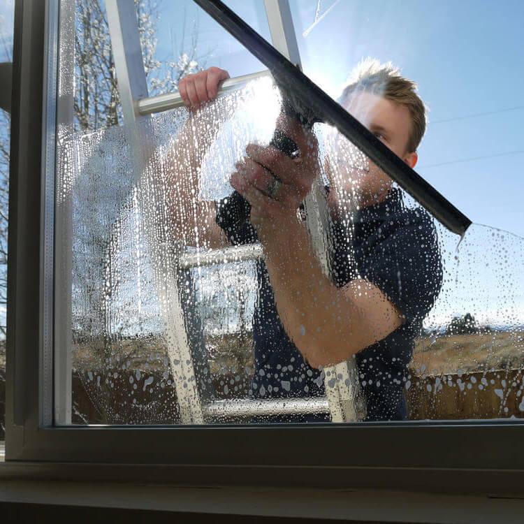 Человек моет окно снаружи дома
