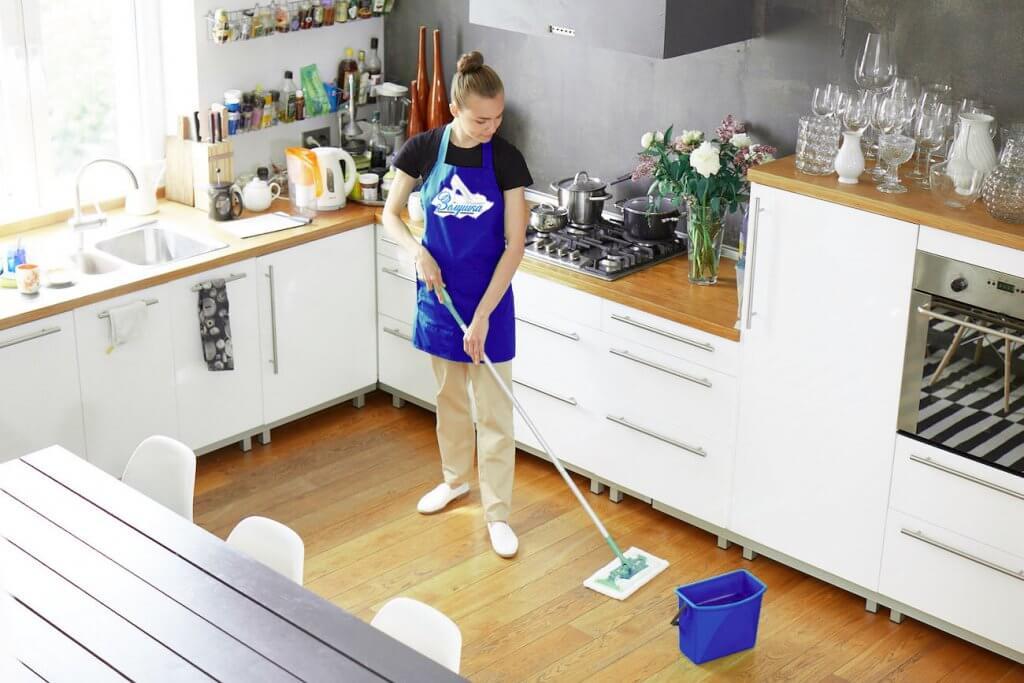 Девушка моет пол кухни шваброй
