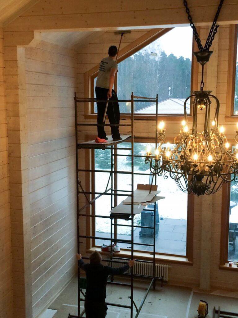 Человек очищает стены высокого помещения с подъемника