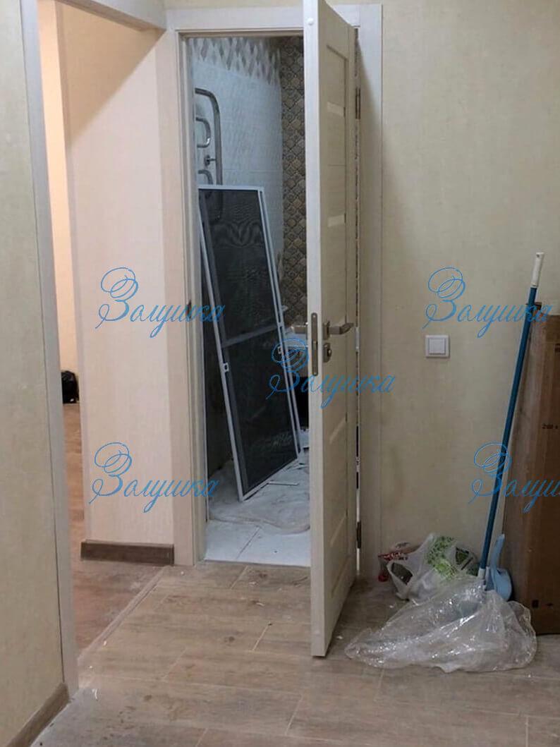 Открытая дверь ванной комнаты после ремонта