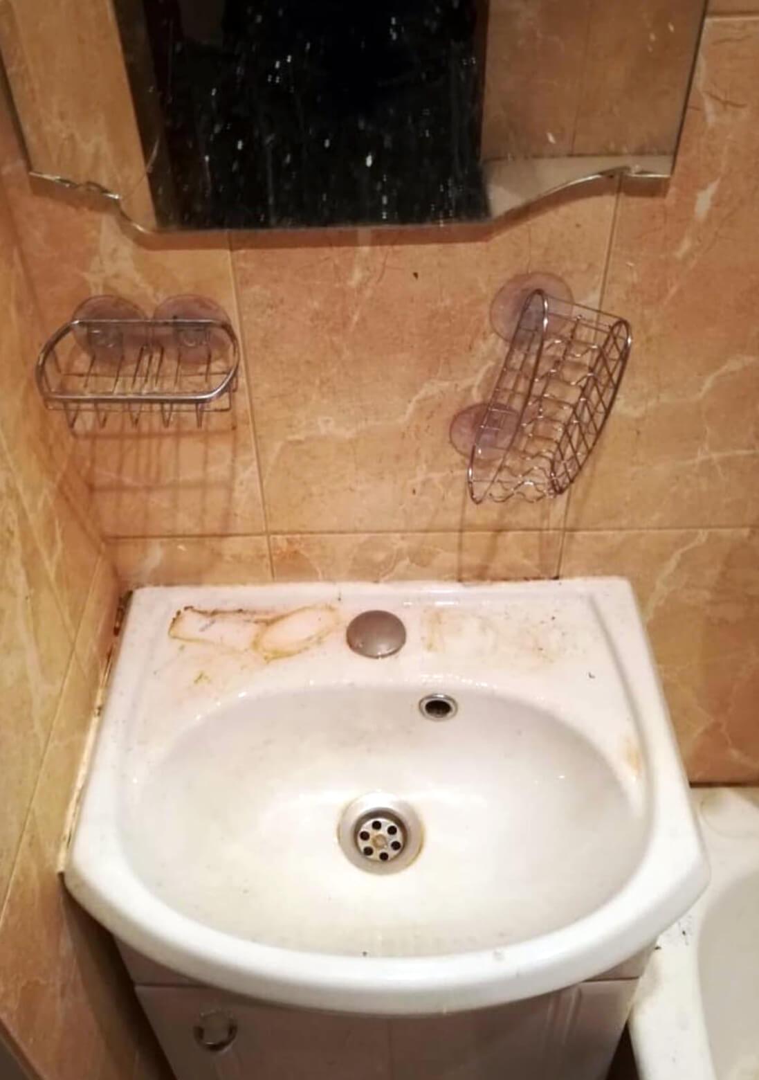 Загрязненная мойка с зеркалом в ванной комнате