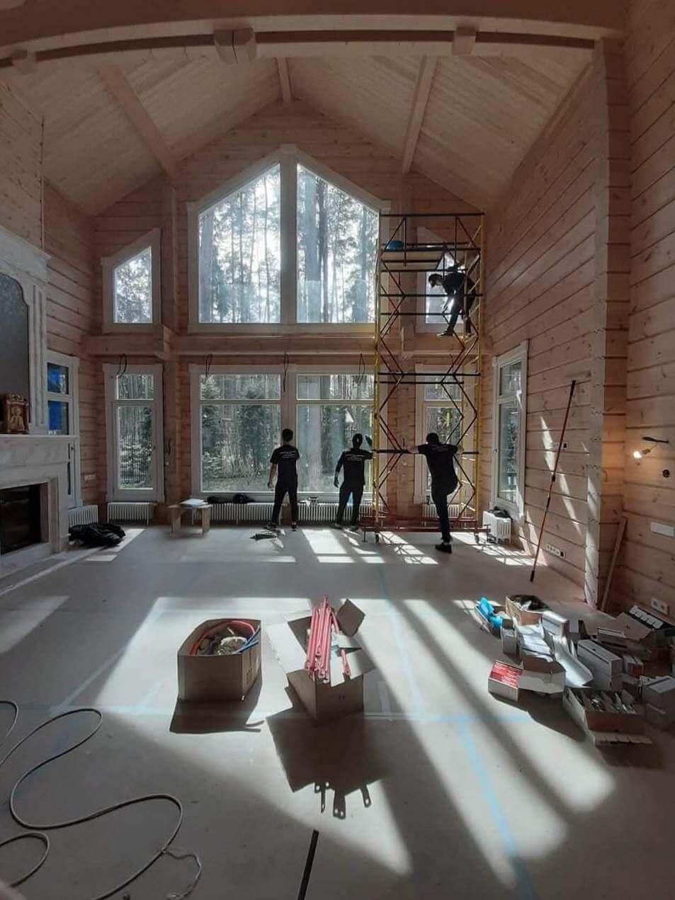 Четыре человека моют окна в высоком холле