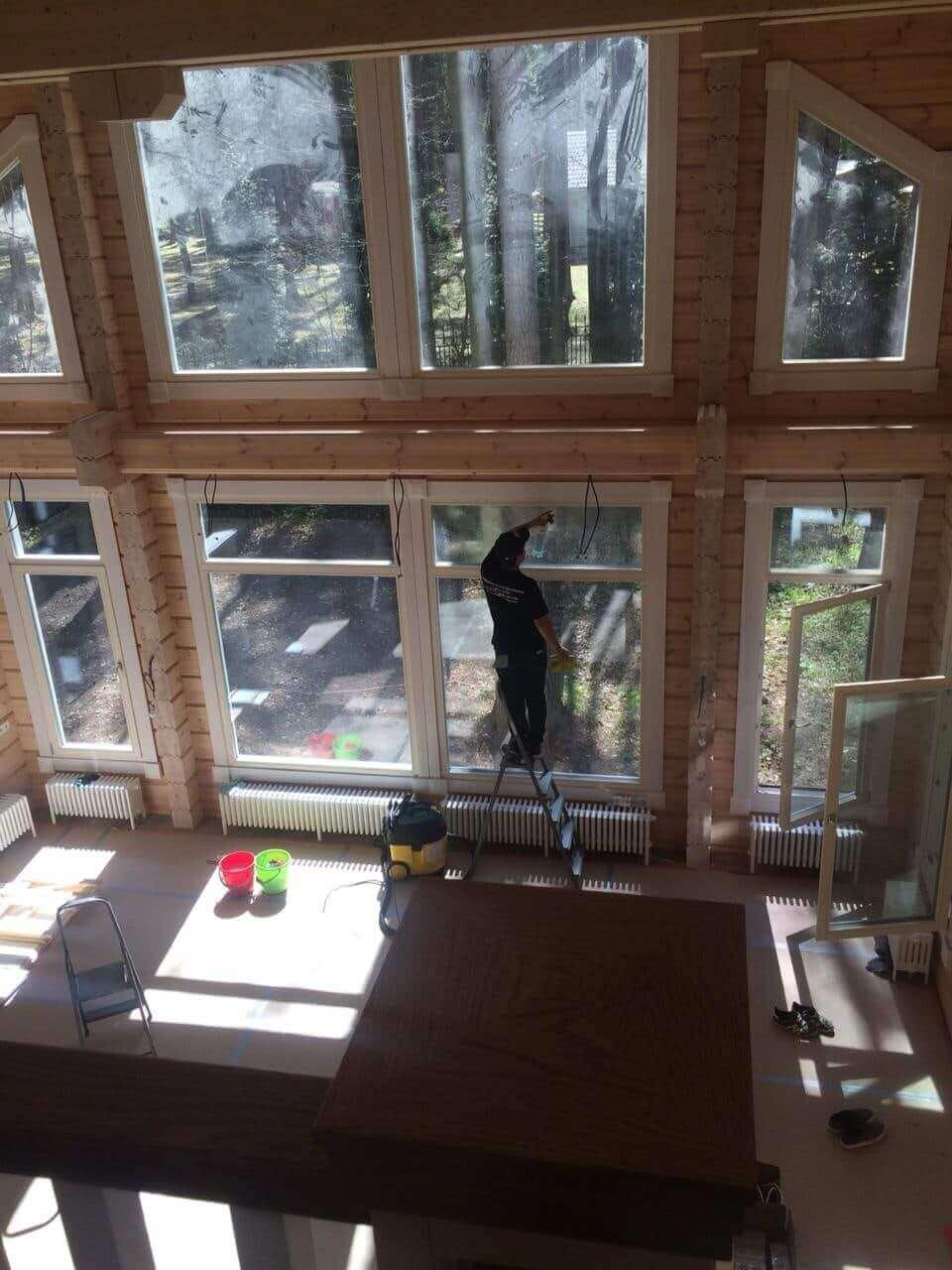 Уборщик моет большие окна загородного дома