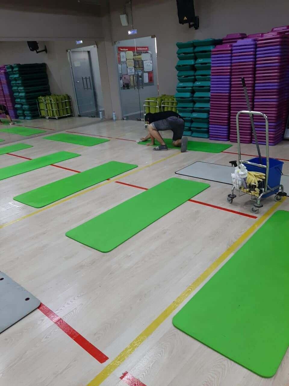 Человек чистит спортивные маты в спортзале
