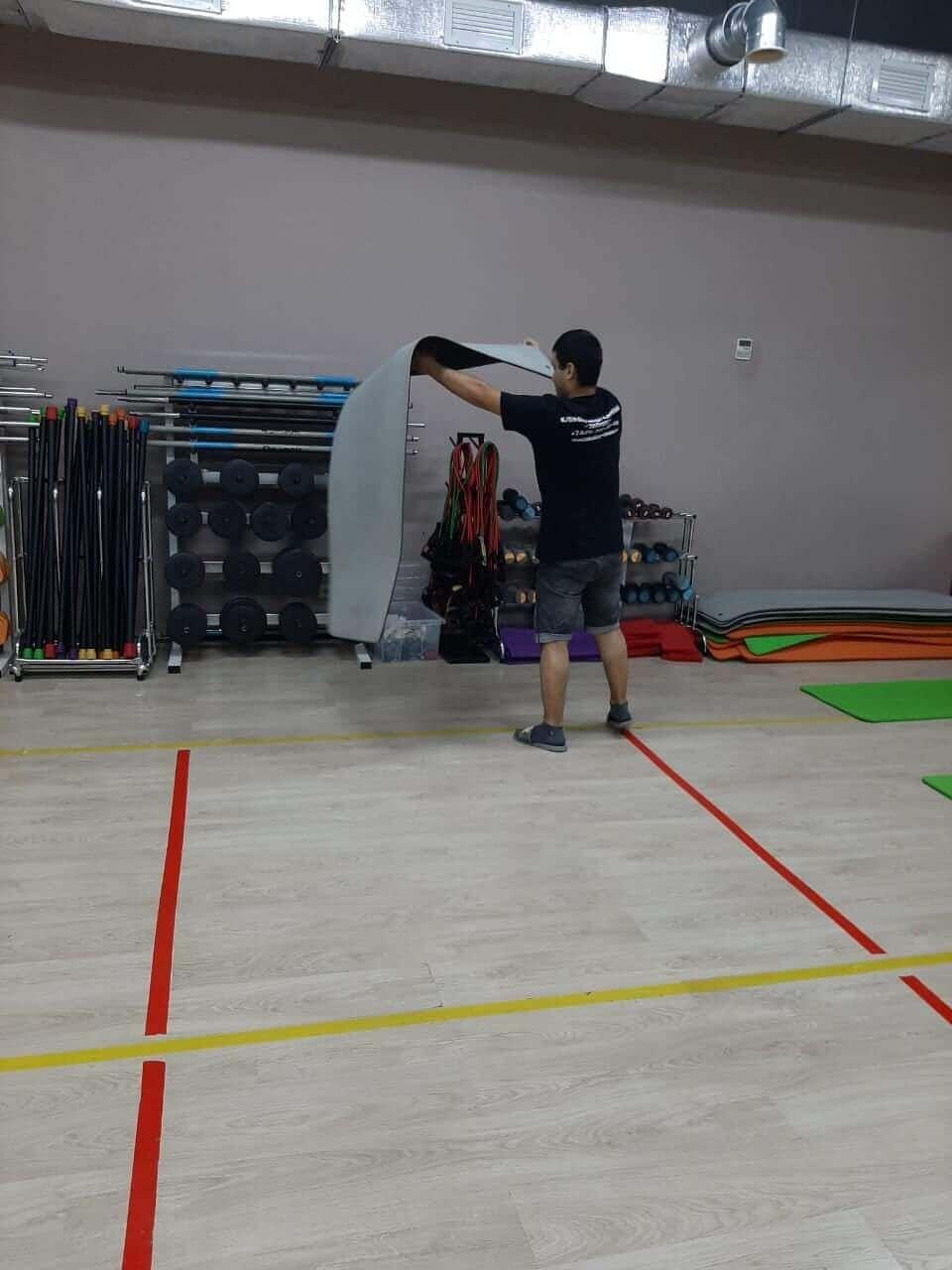 Человек чистит спортивный мат в спортзале