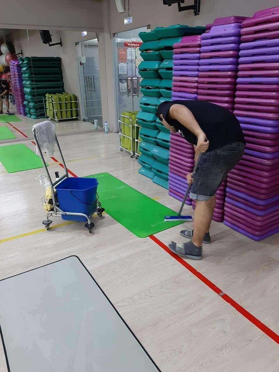 Уборщик моет зеленый мат в зале
