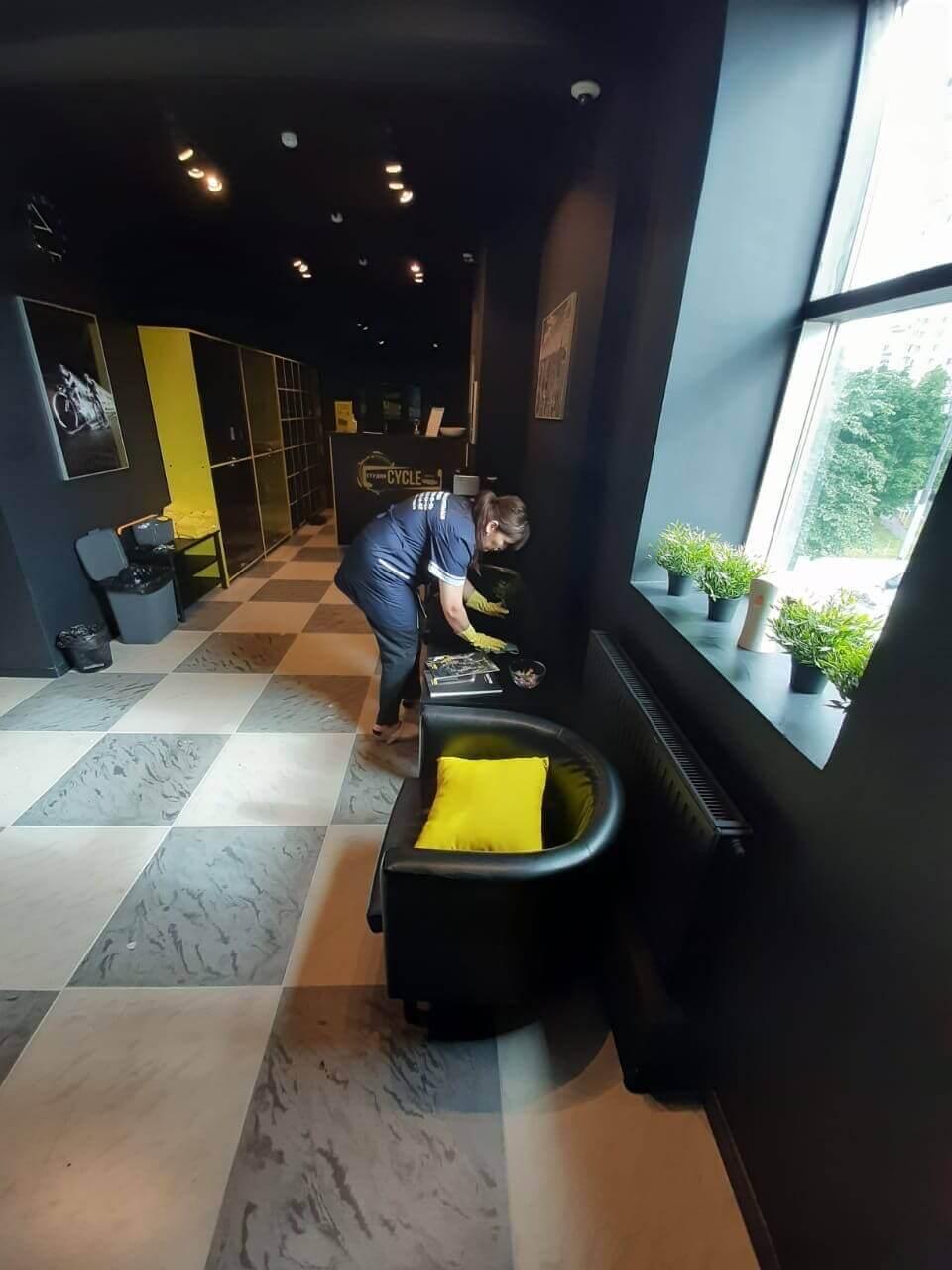 Женщина моет столешницу в общественном помещении