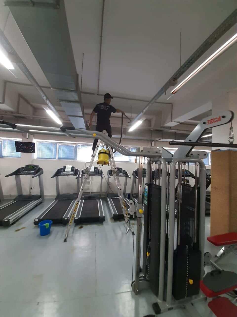 Уборщик моет потолочное оборудование фитнес-клуба