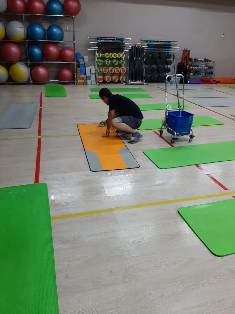 Уборщик моет спортивные коврики в фитнес-клубе