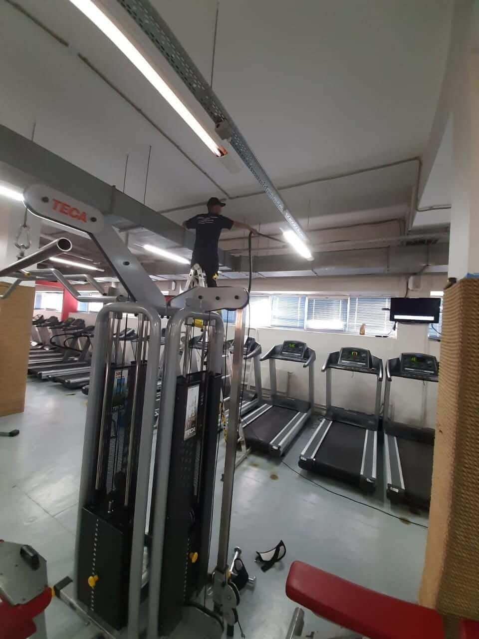 Уборщик моет оборудование в фитнес-клубе