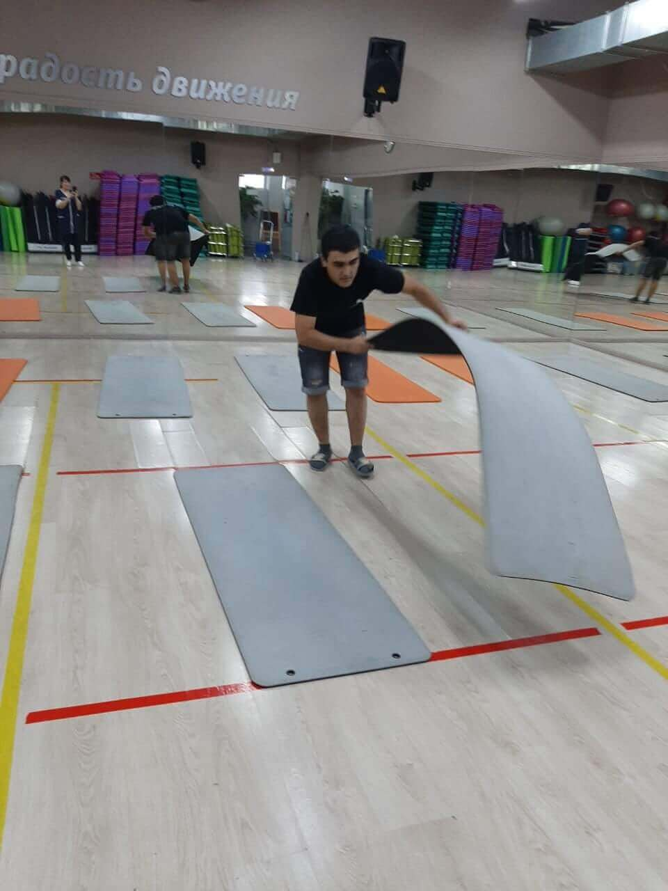 Уборщики моют спортивные коврики в фитнес-клубе