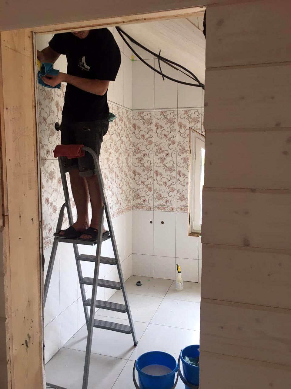 Уборщик на стремянке моет стены комнаты