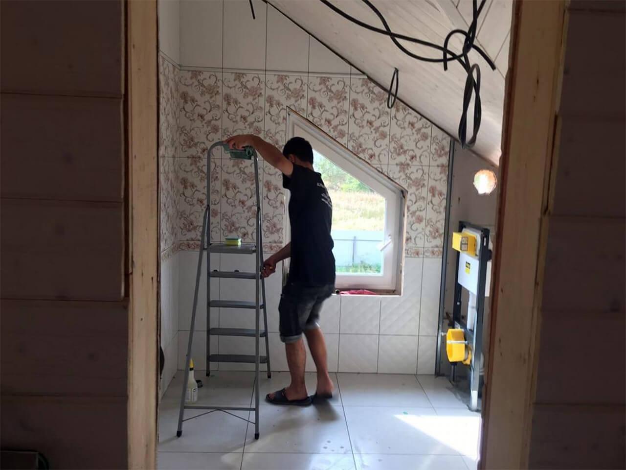 Уборщик со стремянкой моет стены комнаты