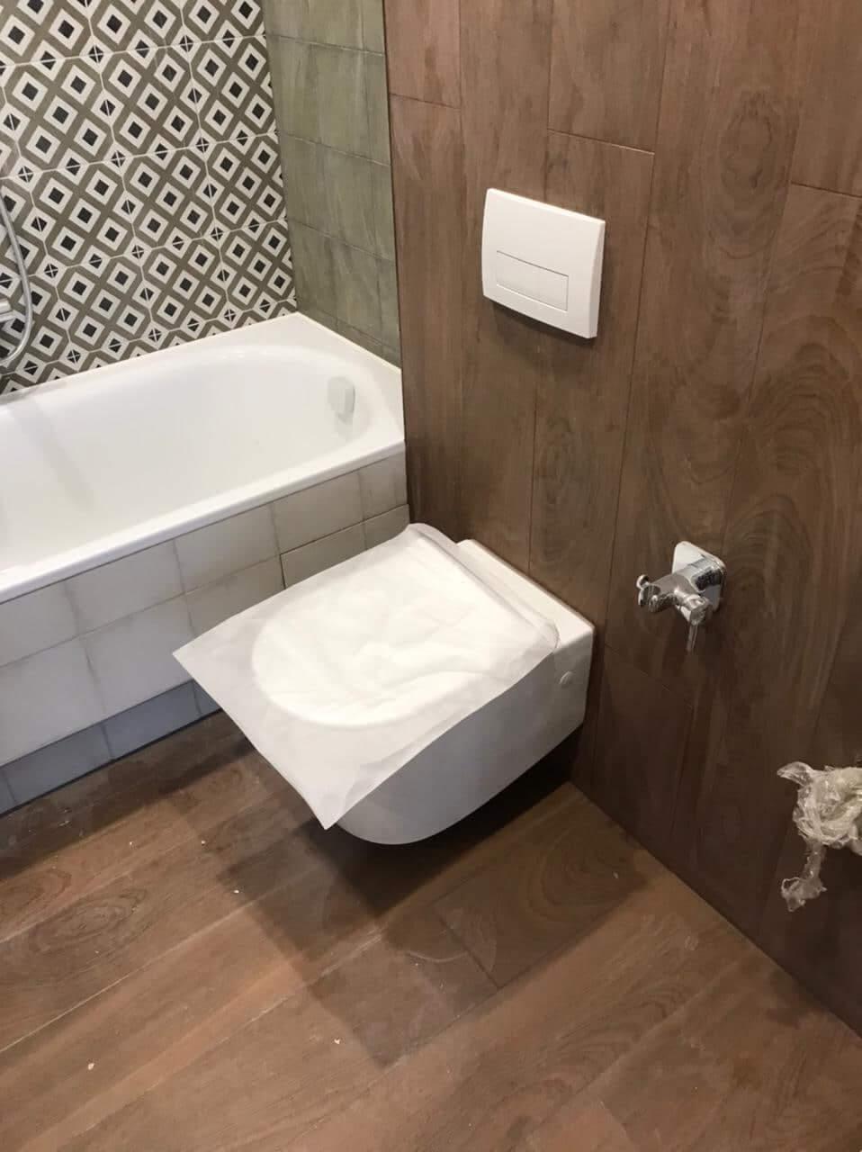 Белый унитаз и ванна перед чисткой