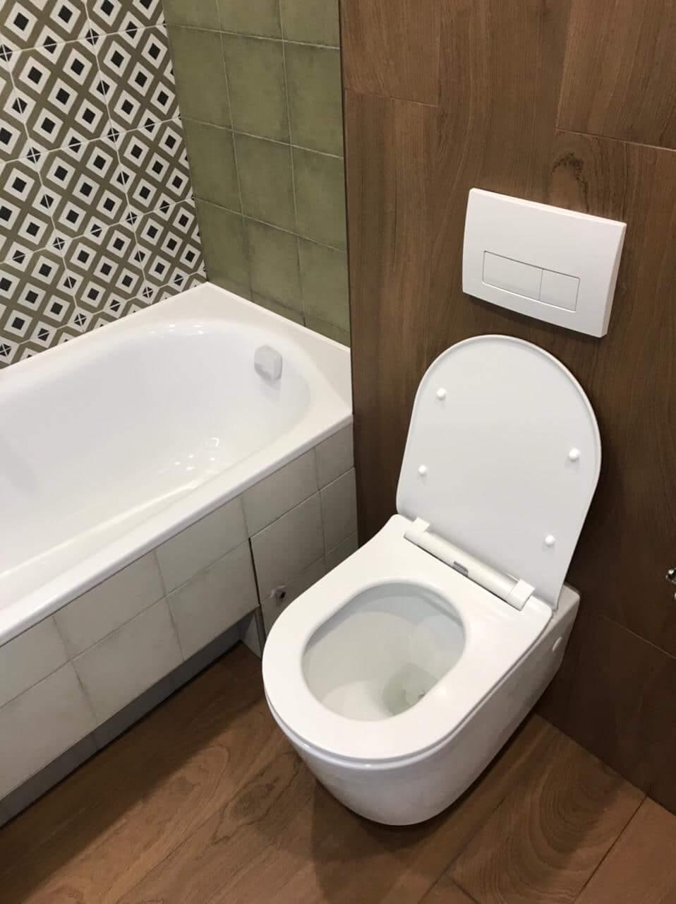 Чистый белый унитаз и ванна