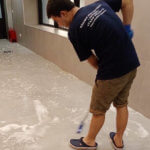 Уборщик моет кафельный пол